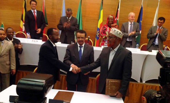 Somali Federal government representative, Farah Sheikh Abdulkadir (left), and Jubaland Administration representative, Sheikh Ahmed Mohammed Madobe (right), exchange signed copies of the agreement on August 28, 2013 at the Hilton Addis Ababa.