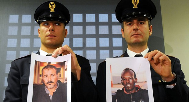 Italian policemen hold pictures of Palestinian Attour Abdalmenem, left, and Somali Mouhamud Elmi Muhidin in Palermo, Sicily. Abdalmenem and Muhidin have been arrested with charges of being responsible of the ship disaster of Oct. 3, 2013 off the coast of Lampedusa