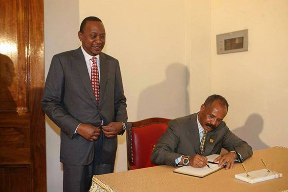 President Kenyatta standing while President Afwerki writing on a book