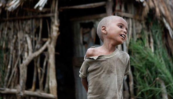 A boy stands outside his tukul as his mother arrives home with the body of his four-year-old sister who died of malnutrition near Sheshemene, southern Ethiopia
