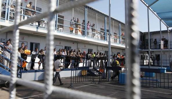 African migrants gesture behind a fence inside Holot, Israel's new Negev desert detention centre
