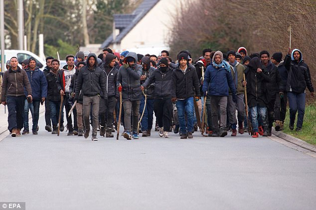 A group of migrants carrying sticks during clashes near the ferry port in Calais, northern France.