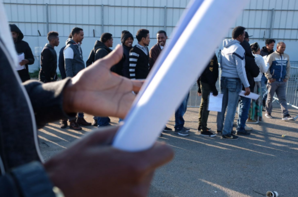 Asylum seekers standing in line to renew their visa