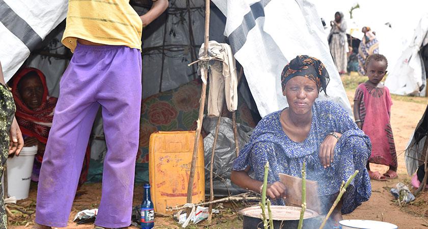 An asylum seeker cooks for her family outside her makeshift shelter.
